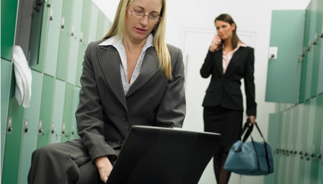 Two businesswomen in locker room using mobile phone and laptop